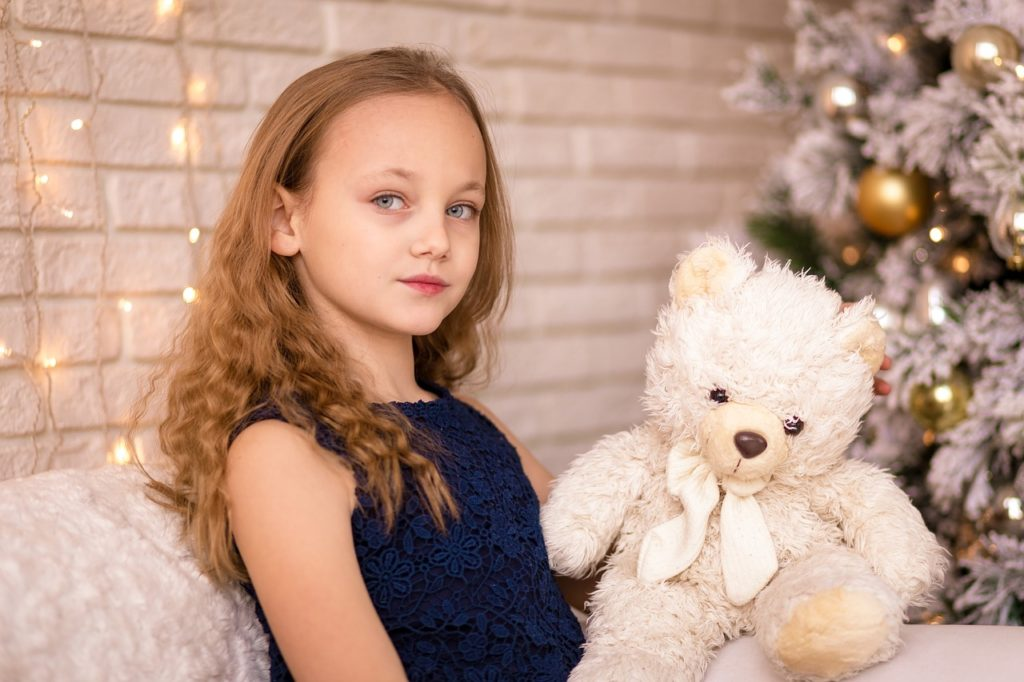A young girl holding a white teddy bear