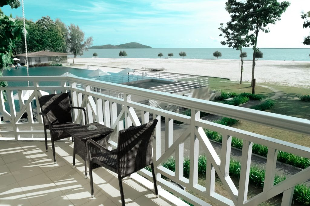 Porch area overlooking a pool and beach