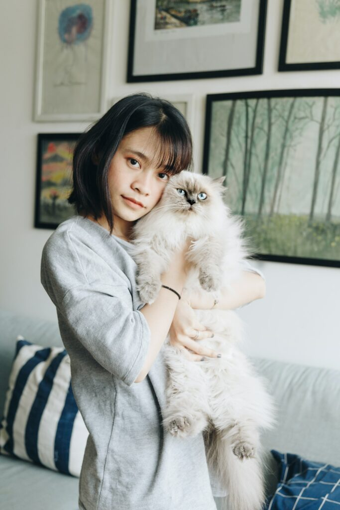 Woman with short dark hair holding a fluffy sand-grey cat in her arms, up towards her face
